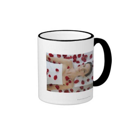 Mujer cubierta en los pétalos de la flor que ponen tazas de café