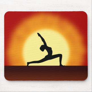 Mujer de la salida del sol de la yoga que presenta tapete de ratones