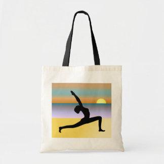 Mujer de la yoga de la playa que presenta la bolsa