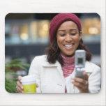 Mujer de negocios sonriente con el teléfono celula tapetes de ratones
