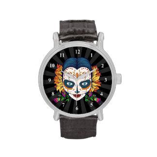 Mujer del cráneo del azúcar con las flores reloj de mano