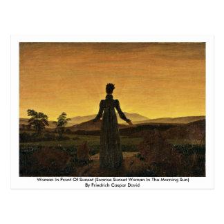 Mujer delante de la puesta del sol postales