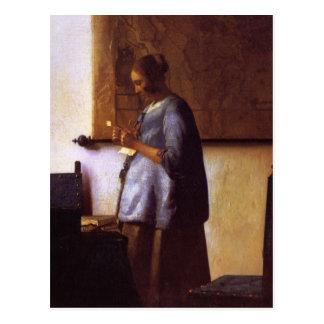 Mujer en azul que lee una letra postales