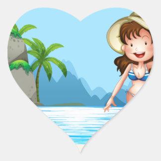 Mujer en bikini en la playa pegatina en forma de corazón