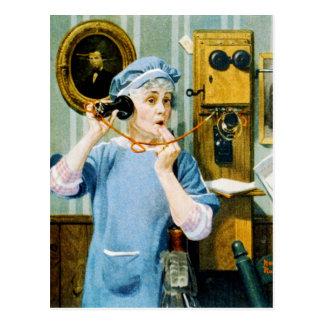 Mujer en delantal usando el teléfono de la pared postales