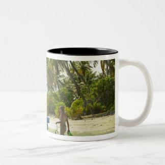 Mujer en el pequeño barco de pesca tradicional, tazas de café