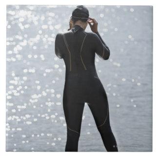 Mujer en el wetsuit que se coloca en roca azulejo cuadrado grande