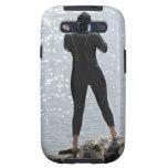 Mujer en el wetsuit que se coloca en roca galaxy SIII fundas