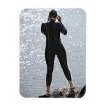 Mujer en el wetsuit que se coloca en roca imán de vinilo