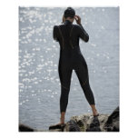 Mujer en el wetsuit que se coloca en roca poster