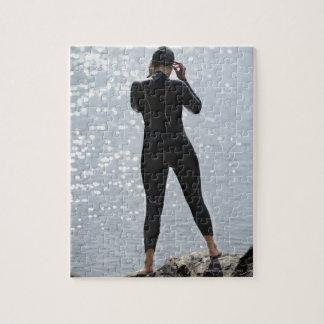Mujer en el wetsuit que se coloca en roca puzzle