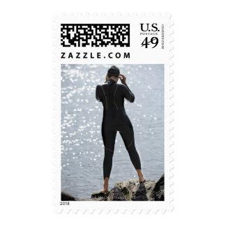 Mujer en el wetsuit que se coloca en roca sellos