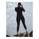 Mujer en el wetsuit que se coloca en roca tarjetas postales