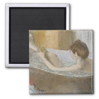 Mujer en su baño, limpiando su pierna con esponja, imán cuadrado