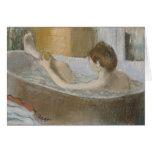 Mujer en su baño, limpiando su pierna con esponja, tarjetón