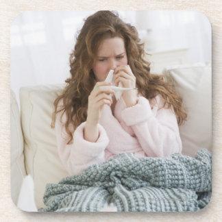 Mujer enferma en el sofá posavasos