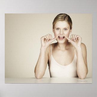 Mujer flossing sus dientes posters