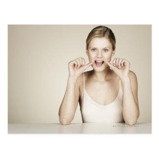 Mujer flossing sus dientes postales