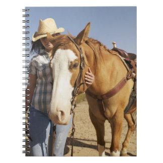 Mujer hispánica que se coloca al lado de caballo notebook