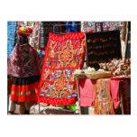 Mujer india peruana que mira las materias textiles postales