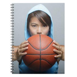Mujer joven con el baloncesto que mira la cámara libreta espiral