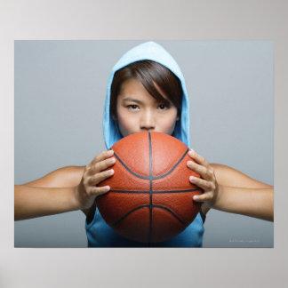 Mujer joven con el baloncesto que mira la cámara póster