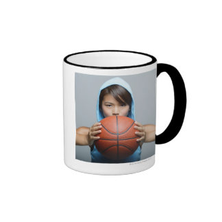Mujer joven con el baloncesto que mira la cámara taza a dos colores