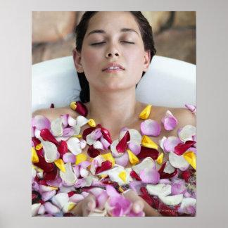Mujer joven hermosa que se relaja en bañera con póster