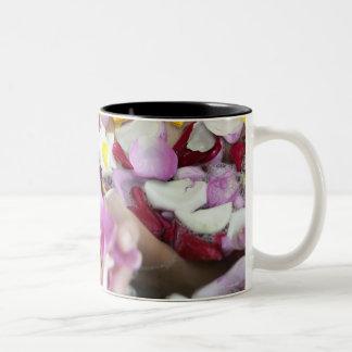 Mujer joven hermosa que se relaja en bañera con taza de café de dos colores