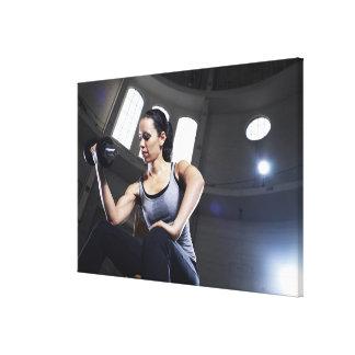 Mujer joven que ejercita con pesa de gimnasia lienzo envuelto para galerias