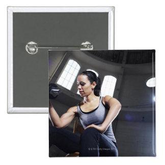 Mujer joven que ejercita con pesa de gimnasia pins