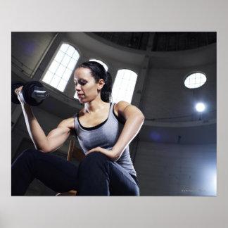Mujer joven que ejercita con pesa de gimnasia póster