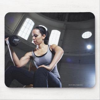 Mujer joven que ejercita con pesa de gimnasia alfombrillas de ratón