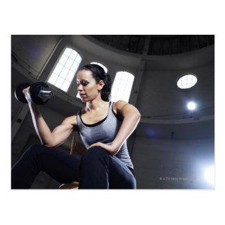 Mujer joven que ejercita con pesa de gimnasia postal