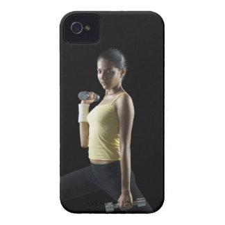Mujer joven que ejercita con pesas de gimnasia iPhone 4 Case-Mate cobertura