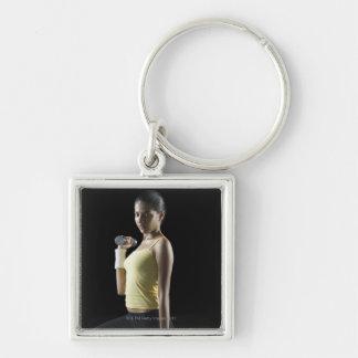 Mujer joven que ejercita con pesas de gimnasia llavero cuadrado plateado