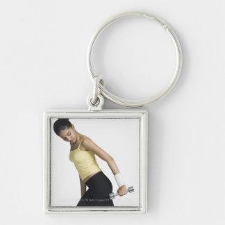 Mujer joven que ejercita con una pesa de gimnasia llavero cuadrado plateado