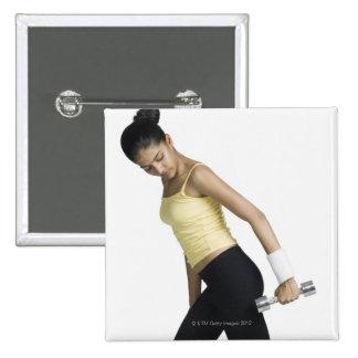 Mujer joven que ejercita con una pesa de gimnasia pins