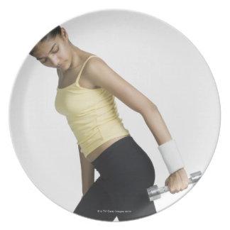 Mujer joven que ejercita con una pesa de gimnasia platos para fiestas