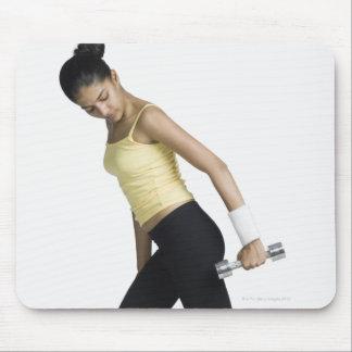 Mujer joven que ejercita con una pesa de gimnasia tapete de ratón