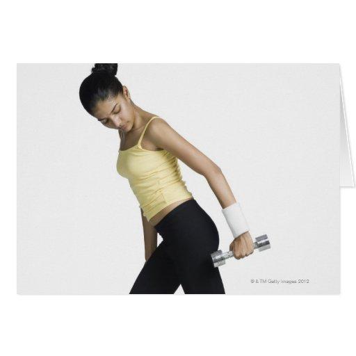 Mujer joven que ejercita con una pesa de gimnasia felicitaciones