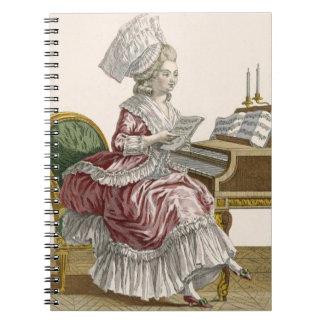 Mujer joven que estudia la música en su clavicordi libro de apuntes con espiral