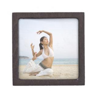 Mujer joven que hace yoga en la playa cajas de recuerdo de calidad