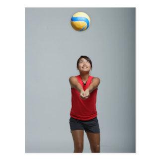 Mujer joven que juega con voleibol postales
