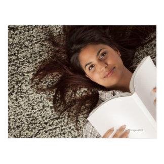 Mujer joven que lee un libro que se acuesta tarjeta postal