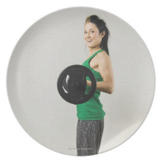 Mujer joven que levanta un barbell. platos