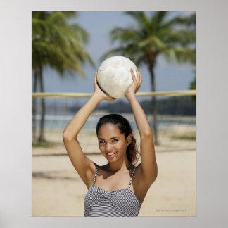 Mujer joven que lleva a cabo voleibol y que sonríe poster