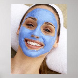 Mujer joven que lleva la máscara facial, sonriendo póster