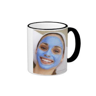 Mujer joven que lleva la máscara facial, taza de dos colores