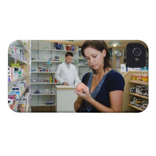 Mujer joven que mira la medicina en farmacia, Case-Mate iPhone 4 funda